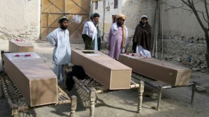 Residents stand near the coffins of victims of a missile attack in Mir Ali on the outskirts of Miranshah