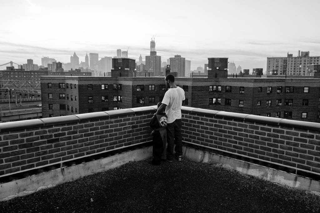 Jerell Willis and son Fidel watching the sun set on downtown Manhattan from the rooftop of their building. Lower East Side NYC, NY.