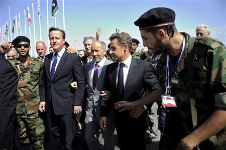 France's President Sarkozy and Britain's PM Cameron are greeted by pro-NTC combatants as they arrive at the Tripoli Medical Center