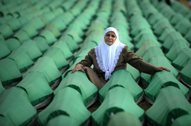 A Bosnian woman mourns over coffins of a newly identified victim of the 1995 Srebrenica massacre during preparation for mass burial at the Potocari memorial cemetery near Srebrenica on July 10, 2010. More than 775 bodies found in mass grave sites in eastern Bosnia will be reburied on 15th anniversary of the Srebrenica massacre. Nearly 8,000 men and boys from the enclave were captured and systematically killed by Bosnian Serb forces in the days after the fall of Srebrenica on July 11, 1995. The victims were shot and interred in mass graves, then reburied haphazardly later in more than 70 sites in a bid to cover up the evidence. AFP PHOTO / DIMITAR DILKOFF (Photo credit should read DIMITAR DILKOFF/AFP/Getty Images)