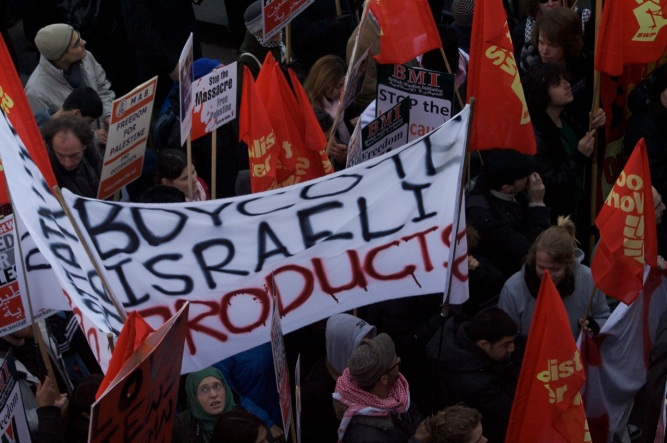 "BDS supporters protesting in London. The poster reads, ""Boycott Israeli Products"" souce Wikipedia"