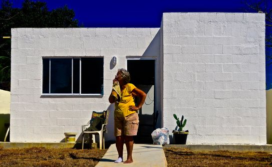 Lady standing outside her newly-built home. Her old one was demolished to make way for the Olympics.