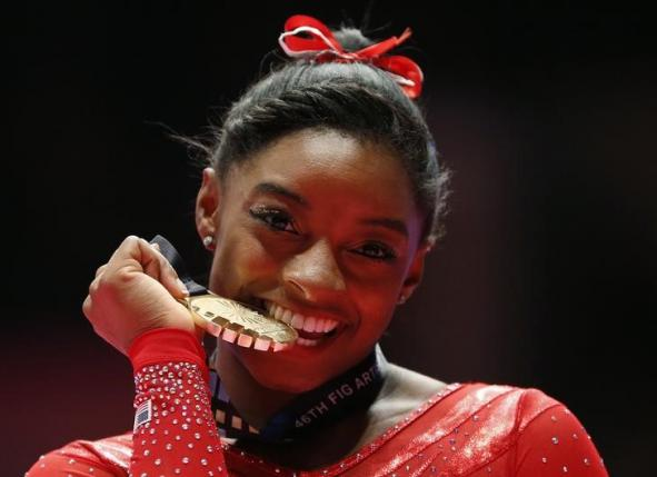 Gold medalist Simone Biles of the U.S poses with her medal after the women's all-round final at the World Gymnastics Championships at the Hydro Arena in Glasgow, Scotland, October 29, 2015. REUTERS/Phil Noble